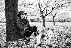 Den unga kvinnan med gulligt hundsammanträde under träd i höst parkerar arkivbilder