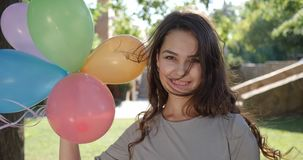 Den unga kvinnan med hänglsen på tänder på bakgrundsgräsplanträden rymmer färgrika ballonger och leenden arkivfilmer