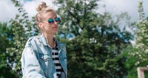 Den unga kvinnan med hörlurar som tycker om tid i en stad, parkerar Royaltyfri Bild