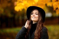 Den unga kvinnan med höstsidor i hand och gul lönn för nedgång gar Arkivbilder
