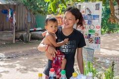 Den unga kvinnan med hennes behandla som ett barn pojken i Cambodja Arkivbild