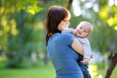Den unga kvinnan med hennes litet behandla som ett barn pojken Royaltyfri Fotografi