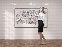 Den unga kvinnan med kaffe och projektet skissar Arkivbild