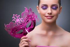 Den unga kvinnan med karnevalmaskeringen arkivfoto