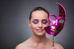 Den unga kvinnan med karnevalmaskeringen royaltyfri foto