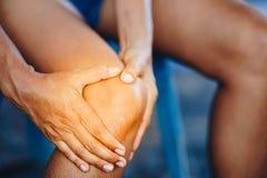 Den unga kvinnan med knäet smärtar arkivbild