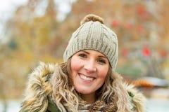 Den unga kvinnan med kopp te står för julträd i vintern, jul marknadsför royaltyfria bilder