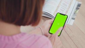Den unga kvinnan med kort hår är den hållande smartphonen med en grön skärm stock video
