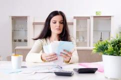 Den unga kvinnan med kvitton i budget som planerar begrepp fotografering för bildbyråer