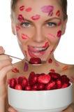 Den unga kvinnan med kyssar på framsida äter hjärtor Arkivfoto