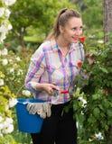 Den unga kvinnan med långa luktrosor för lockigt hår blommar utomhus- Royaltyfria Foton