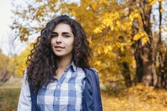 Den unga kvinnan med långt anseende för lockigt hår i höst parkerar royaltyfria foton