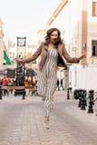 Den unga kvinnan med långt brunt hår studsar lyckligt på bakgrunden av gatan arkivbild
