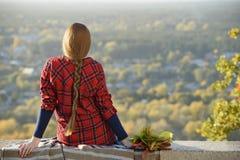 Den unga kvinnan med långt hår sitter på en kulle som förbiser staden royaltyfria foton
