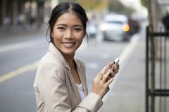 Den unga kvinnan med leende och ilar telefonen på gatan Fotografering för Bildbyråer
