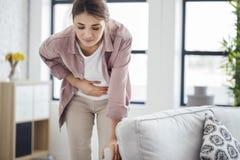 Den unga kvinnan med magen smärtar royaltyfria foton