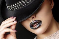 Den unga kvinnan med modesmink rätar ut hennes hatt Royaltyfria Foton