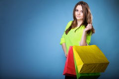 Den unga kvinnan med pappers- mång- färgad shopping hänger lös Arkivfoton