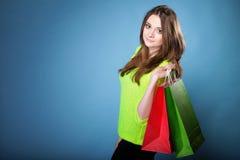 Den unga kvinnan med pappers- mång- färgad shopping hänger lös Royaltyfria Foton