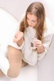 Den unga kvinnan med pillen och exponeringsglas av bevattnar Royaltyfri Foto