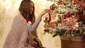 Den unga kvinnan med plädet och Santa Claus i hennes händer ler och dekorerar filialer av julgranen vid leksaker lager videofilmer