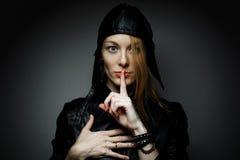 Den unga kvinnan med röda hår som gör en gest för att vara tystnaden, showtystnad, undertecknar in mörk bakgrund Royaltyfria Bilder