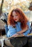 Den unga kvinnan med rött hår i hösten parkerar att ligga på en bänk med skyler och att läsa en bok höstbakgrundscloseupen colors royaltyfri bild
