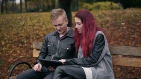 Den unga kvinnan med rött hår och den attraktiva mannen i ett sammanträde för läderomslag på en bänk parkerar in och genom att an stock video