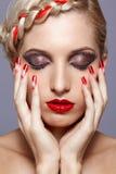 Den unga kvinnan med rött spikar Arkivfoto