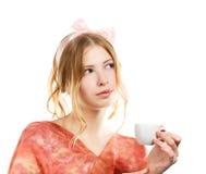 Den unga kvinnan med rosa färger bugar och koppen för vitt kaffe Fotografering för Bildbyråer