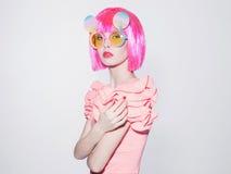 Den unga kvinnan med rosa färger guppar frisyren solglasögon Royaltyfri Fotografi
