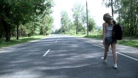 Den unga kvinnan med ryggsäcken som går på vägen tillbaka, beskådar lager videofilmer