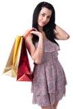 Den unga kvinnan med shopping hänger lös Arkivfoto