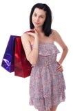 Den unga kvinnan med shopping hänger lös Arkivbild