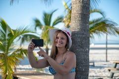 Den unga kvinnan med smartphonen av g?mma i handflatan framme arkivbilder