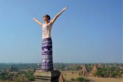 Den unga kvinnan med sned bollspridning räcker att vända mot solen bagan tempel Royaltyfria Bilder