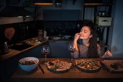 Den unga kvinnan med stängda ögon sitter på tabellen med mat och seger royaltyfria foton