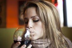 Den unga kvinnan med stängt synar dricka rött vin Royaltyfria Bilder