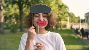 Den unga kvinnan med stora kanter för maskeringen och basker som ler i sommar, parkerar arkivfilmer
