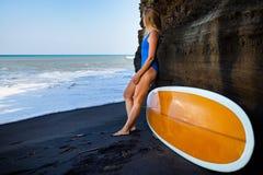 Den unga kvinnan med surfingbrädan går på den svarta sandstranden arkivfoto
