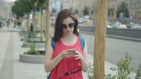 Den unga kvinnan med telefonen spenderar tid på gatan i sommardag lager videofilmer