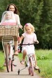Den unga kvinnan med två små flickor som rider cyklar parkerar in Arkivbilder