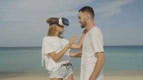 Den unga kvinnan med virtuell verklighetexponeringsglas som möter den stiliga mannen, daterar på stranden lager videofilmer