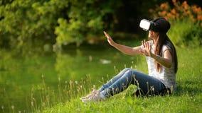 Den unga kvinnan med virtuell verklighetskyddsglasögon sitter nära sjön i staden parkerar Brunetten är Huvud-monterat att använda stock video