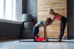 Den unga kvinnan med yogainstruktören i konditionklubban, kamel poserar Arkivfoton