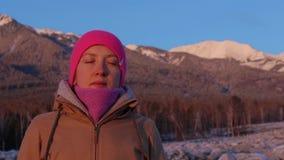 Den unga kvinnan mediterar på foten av bergen lager videofilmer