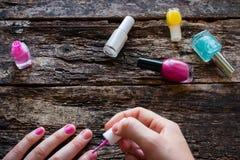 Den unga kvinnan målar henne spikar rosa färgpolermedel på tabellen Arkivfoto
