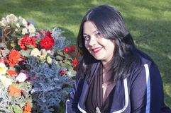 Den unga kvinnan mot bakgrunden av härliga blommor royaltyfri foto