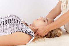 Den unga kvinnan mottar bowen terapi för hennes huvud Arkivfoton