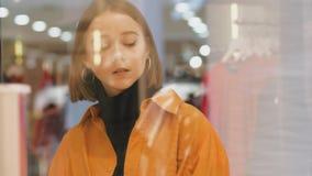 Den unga kvinnan nära shoppar fönstret med trendig kläder stock video
